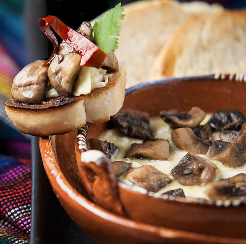 Melted Cheese with Mushrooms in a clay cazuela